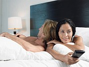 Couple Watching TV and Relaxing on Bed