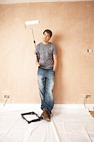 Man standing with paint roller in unrenovated room portrait (thumbnail)