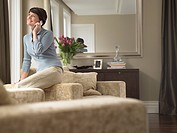 Smiling woman talking on mobile phone in living room (thumbnail)