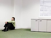 Businessman sitting on floor in corner of office (thumbnail)