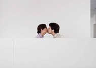 Colleagues kissing in office cubicle
