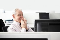 Mature businessman sitting with folded hands in office cubicle