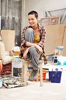 Young female Painter sitting in work site with equipment portrait (thumbnail)