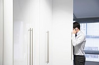Businessman leaning around corner of wall in office Talking on Cell Phone
