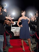 Woman posing on red carpet being photographed by paparazzi (thumbnail)