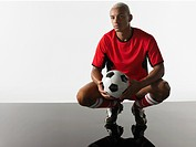 Football player squatting holding ball portrait