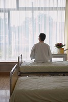 Patient Sitting on Hospital Bed back view