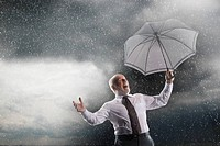 Businessman holding umbrella Laughing in Storm low angle view