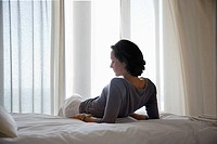 Woman reclining on bed in bedroom