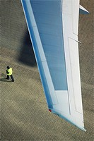 Man walking under airplane wing elevated view