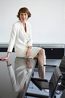 Business woman sitting on conference table portrait