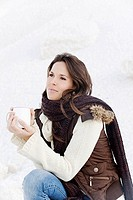 Young woman having a drink in winter outdoor