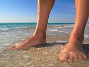 Man's feet in the water at beach