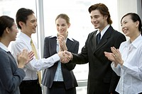 Business people smiling happily and applauding in the office together