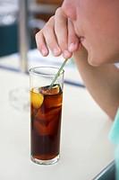 Boy drinking cola through a straw