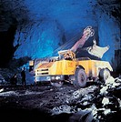Bulldozer loading cupriferous minerals on a semi_truck in a coal mine, Kazakhstan