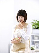 Young woman holding glass bowl of salad, eating, looking away, smiling