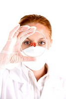 Technician examining petri dish with red drops (thumbnail)