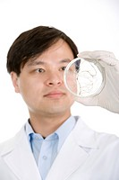 One man working with petri dish, close up