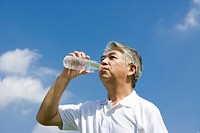 Senior man drinking water against blue sky