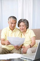 Senior couple looking at paper with laptop on table