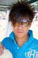 Serious rock musician with spiked hair at his booth Hmong Sports Festival McMurray Field St Paul Minnesota USA