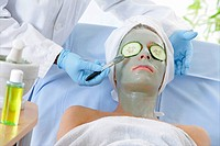 Woman in face mask having cosmetic treatment