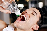 headshot of young man drinking water from bottle in gym