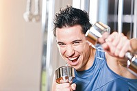 portrait of young man exercising with dumb bells