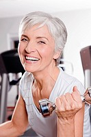 portrait of mature woman exercising with dumb bells