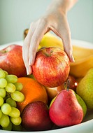 Woman´s hand taking apple from fruit bowl