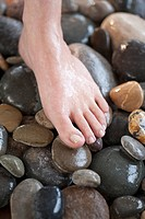 Close_up of woman´s foot on pebbles