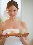 Mid_adult woman wearing towel carrying candles on tray