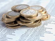 Pile of euro coins on list of share prices