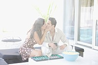 Couple kissing and playing backgammon