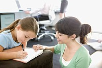 Teenage girl helping little sister with homework