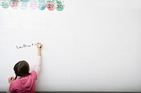 Girl writing on whiteboard in classroom