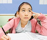Girl writing in workbook in classroom (thumbnail)