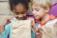 Boy looking in friend's lunch bag at recess