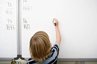Boy writing on whiteboard in classroom