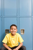 Boy squatting near lockers in school hallway