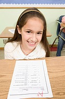Smiling girl with A plus on school paper
