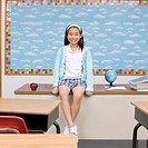 Girl sitting on teacher's desk in classroom