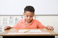 Frustrated boy looking at test in classroom