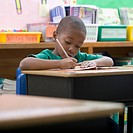 Boy doing school work at desk in classroom