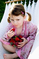 Little girl eating strawberries on a hammock