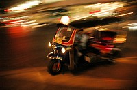 A tuk tuk speeding at night Bangkok, Thailand