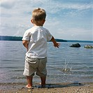 Little Boy Throwing Rocks Into a Lake