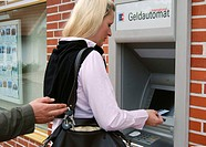 Woman at cash dispenser, pickpocket stealing keys, Germany, cash terminal, creditcard, thief, criminal