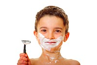 Boy with shaving foam in his face, shaver